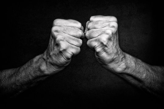 Black and White photo of senior man fists on black background, symbolizing protection and defense, but also attack  and agressivity