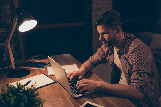 Portrait of attractive programmer, hard worker, busy man in shirt with hairstyle working at night, taking work at home, looking at screen of laptop, sitting in work place, holding hands on keypad