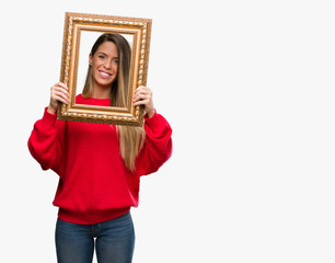 Beautiful young woman holding vintage frame with a happy face standing and smiling with a confident smile showing teeth