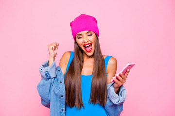Charming and happy girl joyfully clasps her hand in a fist and holding the phone in her hands isolated on bright pink background