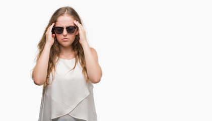 Young blonde woman wearing sunglasses with hand on head for pain in head because stress. Suffering migraine.