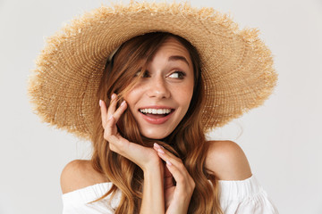 Photo of elegant young woman 20s wearing big straw hat looking aside with cute smile, isolated over white background