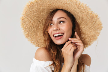 Image of content charming girl 20s wearing big straw hat looking aside with happy smile, isolated over white background