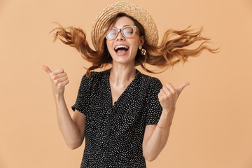Portrait of joyful pretty woman 20s wearing straw hat and sunglasses laughing with shaking hair, isolated over beige background