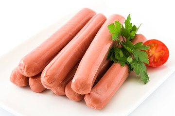 Raw sausages in a white plate isolated on white background