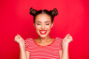 Close up portrait of happy young woman with toothy smile clasp hands in fists and celebrate achievement goal isolated on red bright background