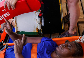 An African migrant rests inside NGO Proactiva Open Arms rescue boat in central Mediterranean Sea