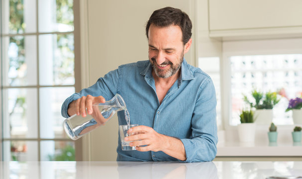 Middle age man drinking a glass of water with a happy face standing and smiling with a confident smile showing teeth