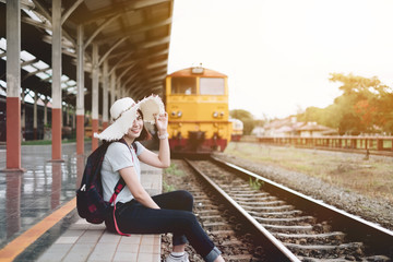 Beautiful young woman waiting for a train on the platform of Chiang Mai Train Station, Thailand