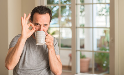 Middle age man drinking coffee in a cup doing ok sign with fingers, excellent symbol