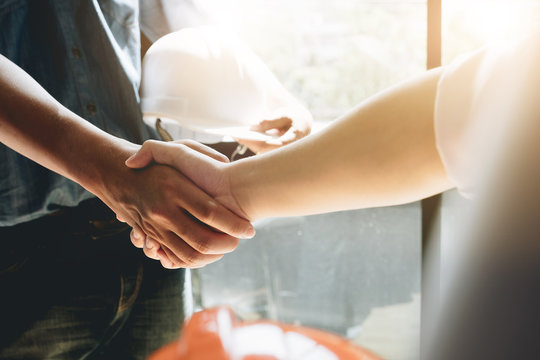 Engineers or architecture shaking hands at construction site for architectural project, holding safety helmet on their hands.