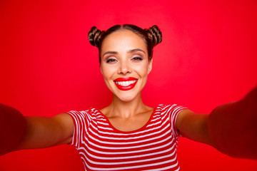 Video call of pretty, charming and smiling young girl with modern hairdo. Model shooting selfie on front camera with two arms isolated on red background