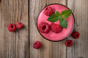 Raspberry shake or smoothie, made with  raspberries and  ice cream or non dairy milk on wooden rustic background, top view