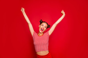 Happy celebrating winning success woman  isolated on red baskground with arms raised up above her head. Success and life goals concept
