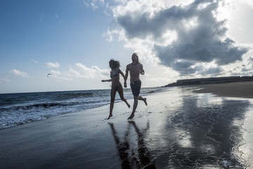 couple of friends with relationship run together on the shore near the ocean and the waves enjoying the summer holiday. blue sky from evening. young beautiful people in outdoor leisure activity