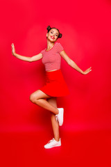 Full-legh and full-body vertical photo of charming, lovely and cute young woman isolated on red vivid background