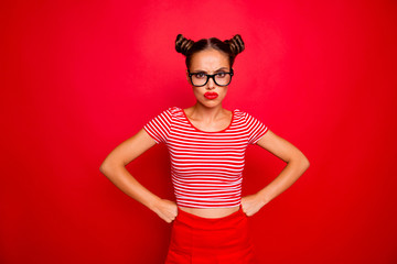 Strict teacher! Portrait of grimacing offended young gorgeous woman model with with hands on waist and bun hairstyle isolated on red background