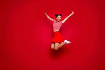 Full-length full-size view of jumping laughing and pretty woman dressed in colourful bright clothes isolated on red background