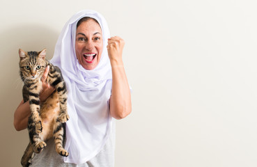 Arabian woman wearing white hijab holding a cat screaming proud and celebrating victory and success very excited, cheering emotion