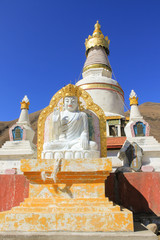 White Buddha and stupas in a small Tibetan temple in a remote little town called Xinduqiao, China. Religious architecture building