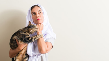 Arabian woman wearing white hijab holding a cat serious face thinking about question, very confused idea