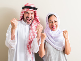 Middle age arabic couple, woman and man screaming proud and celebrating victory and success very excited, cheering emotion