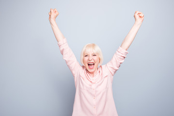 Old blonde glad excited lady smiling, laughing, raising hands up, opened mouth, over grey background, copy space