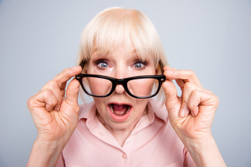 Portrait of old adult blonde caucasian lady shocked scared surprised wearing putting down eye glasses, over grey background, isolated