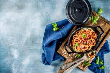 Italian cuisine, Calamari Fra Diavolo, spaghetti pasta marinara with seafood, light blue background copy space top view