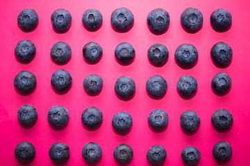 Top view of fresh ripe blueberries on pink background