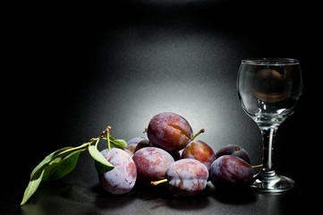 Plums ripe and juicy shot close-up on a dark background and a glass of wine