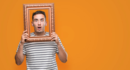 Handsome young man looking through vintage art frame scared in shock with a surprise face, afraid and excited with fear expression
