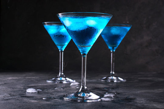 Blue cold cocktail in martini glass with ice and clear dew drops on  glass on a dark concrete background
