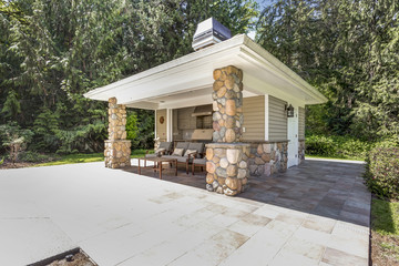 Chic outdoor kitchen space with stone columns