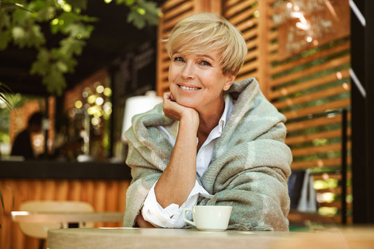 Joyful mature woman wrapped in blanket