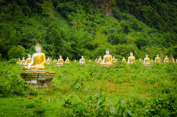 Painted Sitting Buddha figures aligned in a field near Hpa-An, Myanmar.