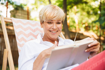 Smiling mature woman reading a book while resting