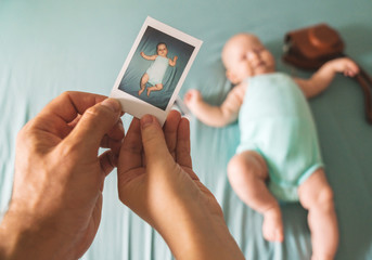 The first photo of a newborn in the hands of a man and a woman against a child. Instant photo in Polaroid style on heavy paper.