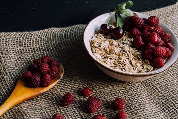 Delicious, healthy breakfast.Porridge with berries.Ecofriendly.Oatmeal porridge with raspberries and cherries.The idea for breakfast on black background. Natural, dietary food.Good morning. Life style