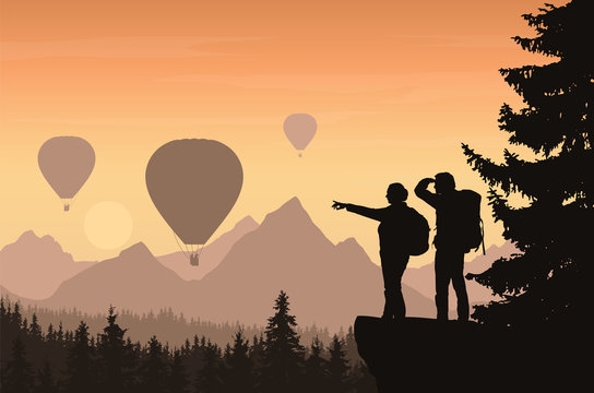 Two hikers looking down into the valley between mountains with forest and flying hot air balloons
