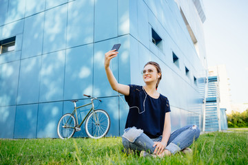 Amazing stylish girl smiling while takes a selfie on smartphone, enjoying listening to music in headphones, during sitting on grass, outdoors.