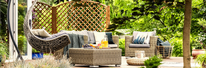 Cozy hanging egg chair, stylish garden furniture and fruit on a wicker table on a spacious terrace...