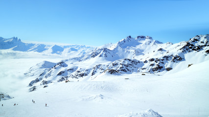 Panorama of rugged alpine peaks with wide skiing slopes and valley covered with low clouds, 3 Valleys Val Thorens winter resort, Alps, France .