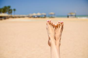young woman feet on sandy sea beach horizon background