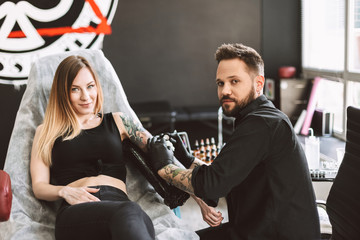 Tattooed girl and professional tattooer happily looking in camera doing tattoo on hand by tattoo machine in studio