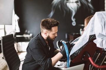 Professional tattoo master dreamily doing tattoo on girl hand using tattoo machine in studio