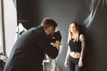 Tattoo master taking photos on camera of tattooed girl standing on black background in modern studio