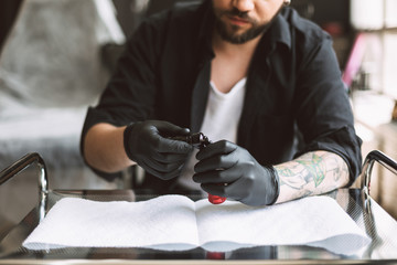 Close up professional tattooer in black gloves preparing equipment for work in studio