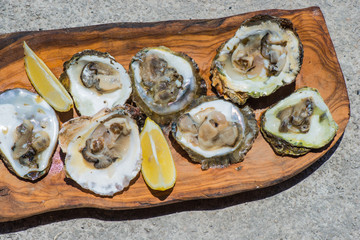 Oysters with lemon on wooden plate. Top view