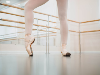 Close up legs in pointe. Training before performance. Woman practicing in classical ballet in tutu dress in gym or ballet hall. Performing sensual dance.
